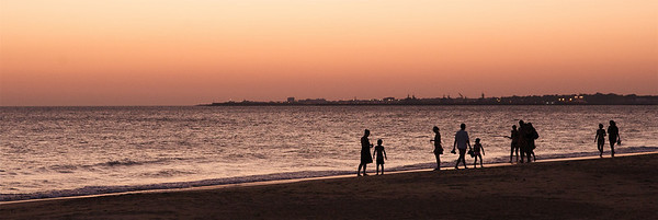 People on the beach at sunset in Cadiz, Spain