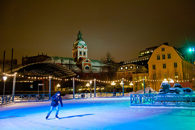 Man ice skating at night in downtown Stockholm
