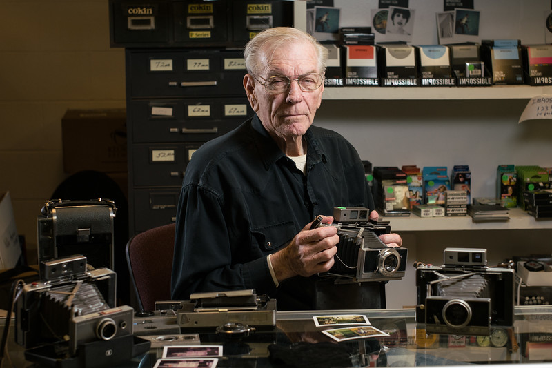 Don Puckett, Owner of Don's Used Photo Equipment holding his custom Polaroid camera
