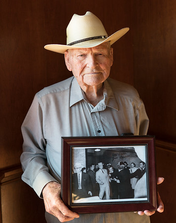 'James Leavelle at 96 holding a photo of himself handcuffed to Lee Harvey Oswald as he is shot by Jack Ruby in 1963'