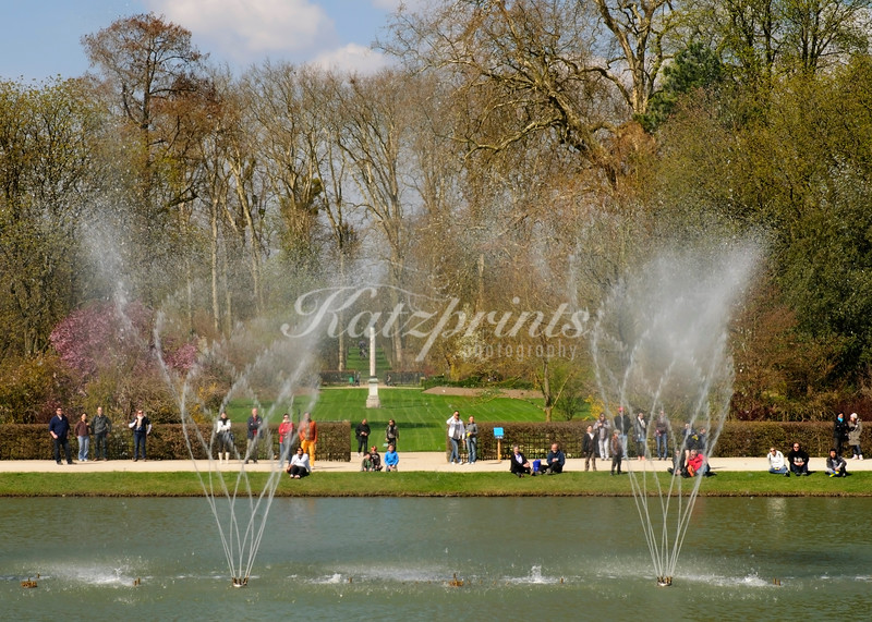 Visitors enjoy a fountain display on a spring day in Versailles