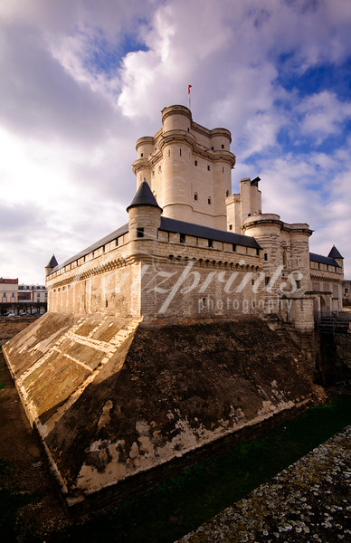 The Château de Vincennes is a massive medieval castle surrounded by a deep stone lined moat in the town of Vincennes near Paris