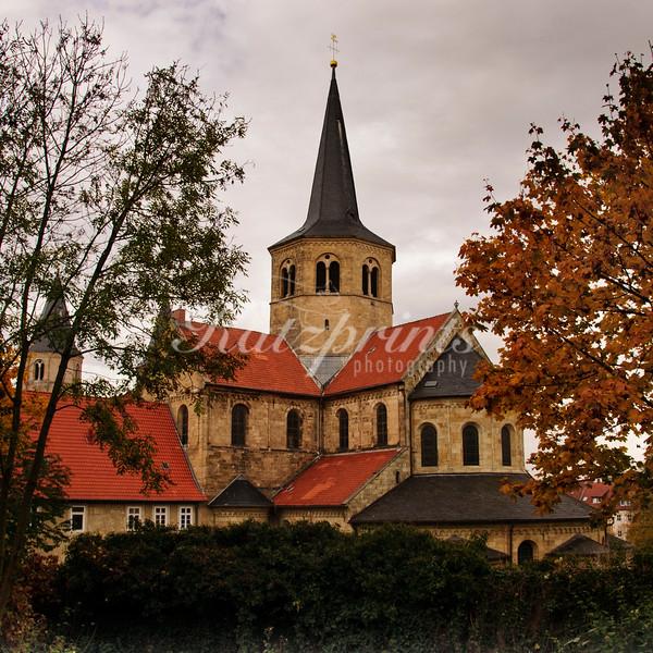 The Basilika Sankt Godehard in Hildesheim is framed by trees.