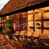 Warm atumn afternoon light falls onto an old barn, tables and benches in Germany.