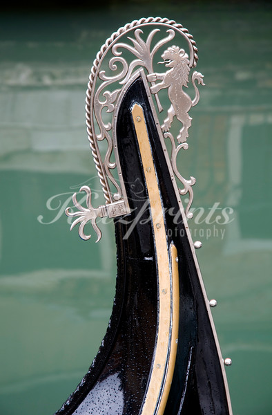 Raindrops adorn the front and fèrró of a Venetian gondola