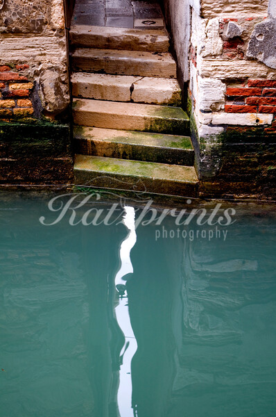 Stairs lead towards the water of a canal in Venice