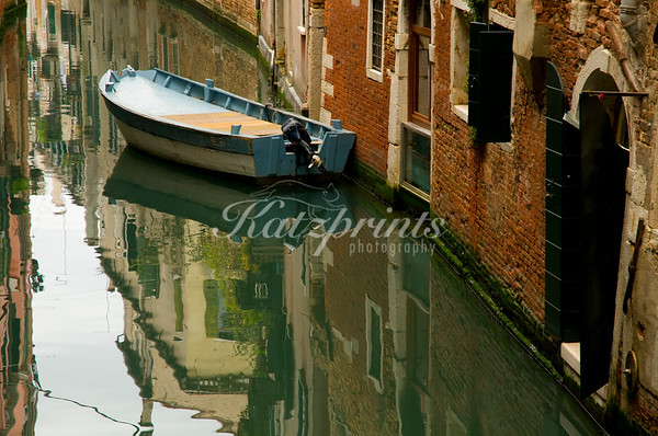 Reflection of a boat and houses in a little canal in the beautiful city of Venice