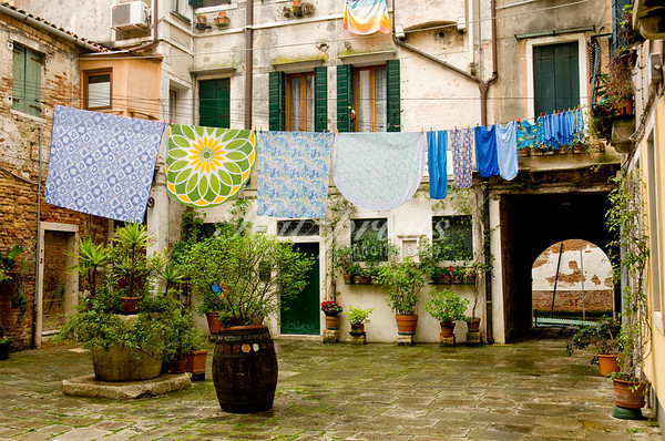 A laundry line spans a courtyard on a rainy day in the city of Venice