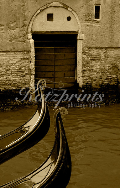 Two gondolas with front decoration on little canal in Venice (sepia)