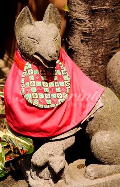 Red-bibbed fox (inari) statue at the Gojo shrine in Ueno Park, Tokyo