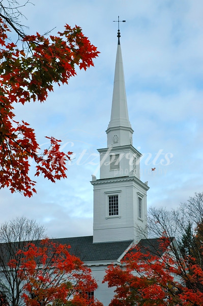 A leaf is falling in front of white church in Hanover, New Hampshire