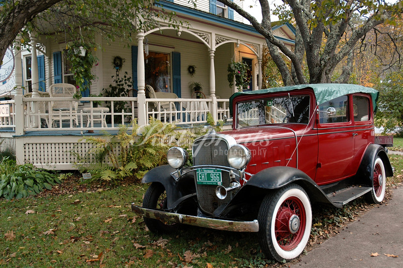 A classic car is parked in front of a Victorian house in Vermont