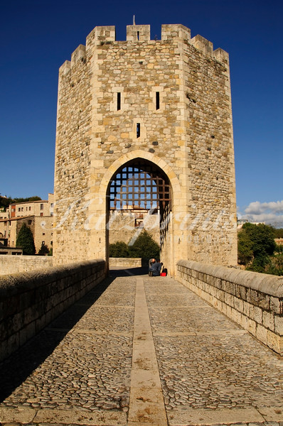 Two men work on one of the towers of Besalú's 12th century bridge across the Fluvià. This striking bridge was built with riverrocks.