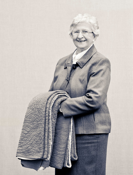 Min<br /> <br /> In Memory of Jill Curry 1956-2008<br /> Photograph of Min Jackman (Jill's mother) holding a quilt made by Jill's Great Grandmother and friends circa 1920.