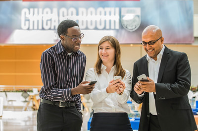 Marshall Smith, left, Chelsea Vail and Mukul Kumar demonstrate the new Booth app on their phones, Thursday, August 20, 2015 at the Booth School. (Photo by Jean Lachat)