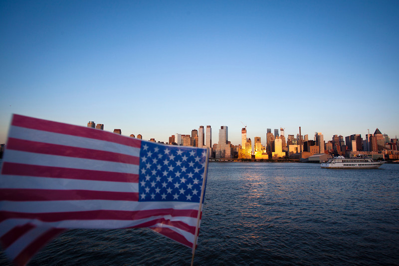 NEW YORK CITY. MANHATTAN SEEN FROM THE HUDSON RIVER. 4TH OF JULY INDEPENDENCE DAY - AMERICAN FLAG.