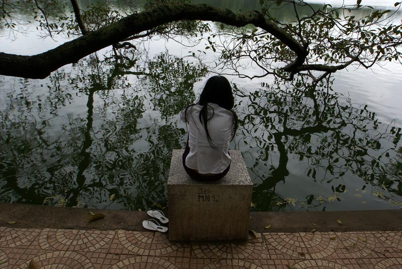 HOAN KIEM LAKE. VIETNAMESE LADY SITTING. HANOI.