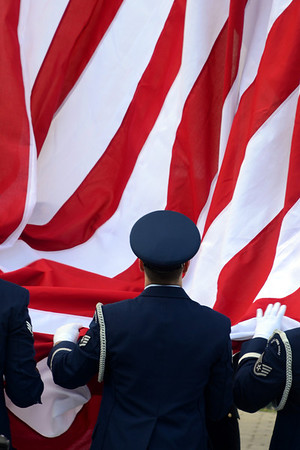 Servicemen a flag during a dedication on Baltimore's Federal Hill