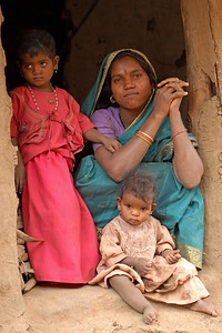India: Mother with her two daughters was sitting at the entrance of her house  in a village near Nagpur, Maharashtra. Jan 2007.