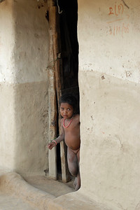 India: Little girl standing outside the door to her house in a village near Nagpur, Maharashtra, India.