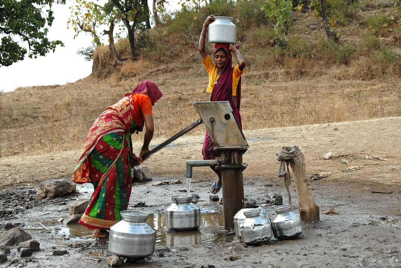 Women using a hand pump to pull up ground water for home-use.  (MH, Maharashtra, India)