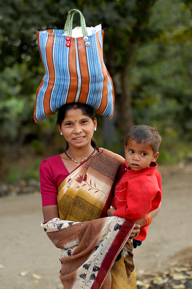 Balancing Act.<br /> Lady with a bag on her head and her boy in arms in rural MP (Madhya Pradesh), India.