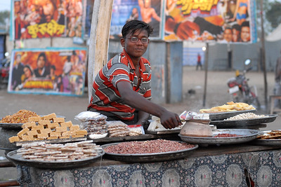 Food stall in the village. Selling an assorted sweets and other snacks. The young boy is heating some peanuts with a charcoal-pot.