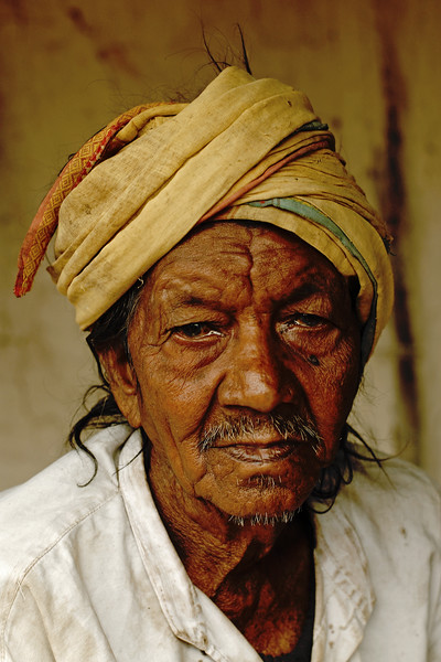 India: Close up portrait of an elderly person. This old man had a very staid expression and looked like he had seen many ups and down in his life. Sitting outside his house, he was watching as the people passed by in a village near Nagpur, Maharashtra. Jan 2007.