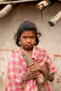 India: Portrait of a girl in a village near Nagpur, Maharashtra. This girl had drapped the torn cloth over herself and with her earings gave a pose for a picture. Jan 2007.