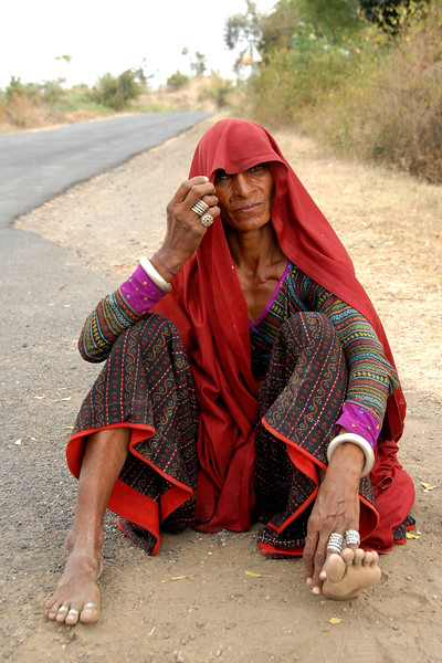 India:This lady from Rajasthan dressed traditionally was travelling with her family and were sitting waiting for a ride in a village near Nagpur, Maharashtra. Jan 2007.