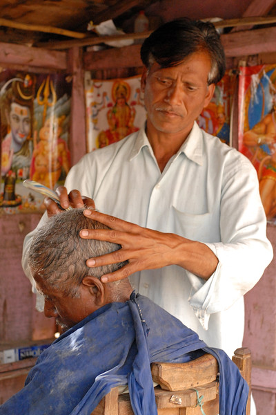 Getting a hair cut & shave in a rural barber shop in MP (Madhya Pradesh), India.