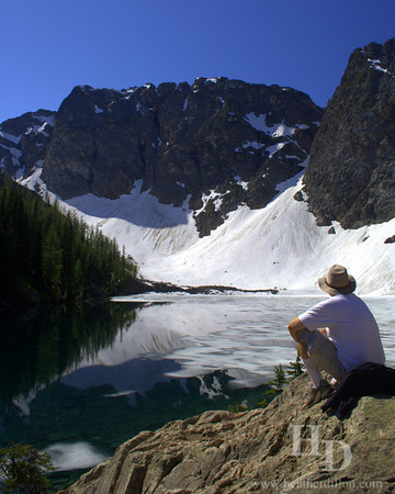 Hiker admires ice on Blue Lake in North Cascades National Park, Washington.