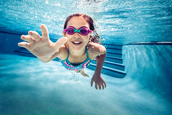Young girl swimming underwater.