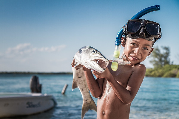 A young boy holding a fish with sharp teeth.