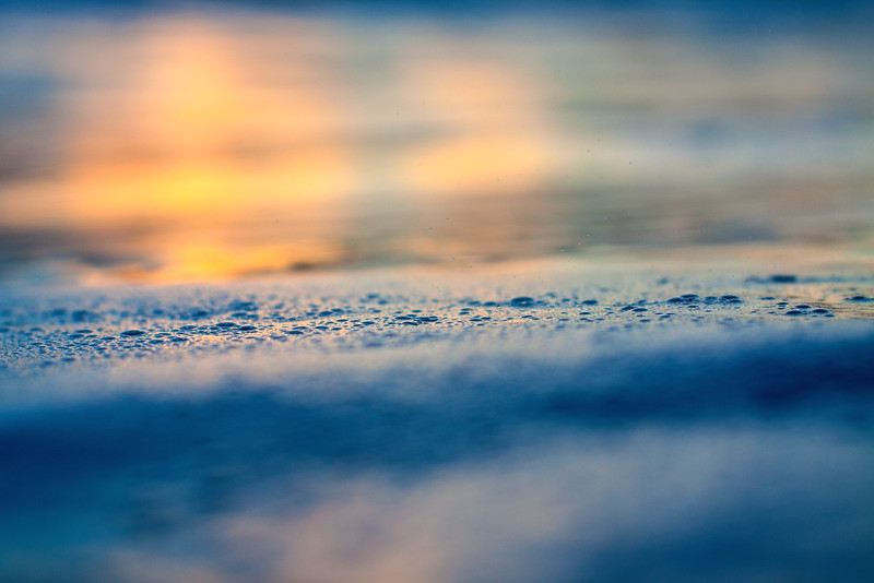 Sunsets over the foam of a wave past.