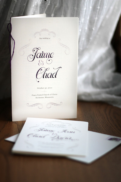 Corresponding wedding program hand-bound with plum binding floss stands with the Z-fold wedding invitation.