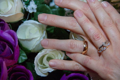 Wedding Photo of the Bride and Groom's hands over the Bride's flowers.