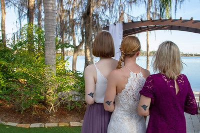 Wedding Photo of the Bride, Maid of Honor, & Mother of the Bride showing off matching tattoos.