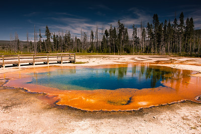 hot colored pools created by water heated by magma underneath and thermophiles