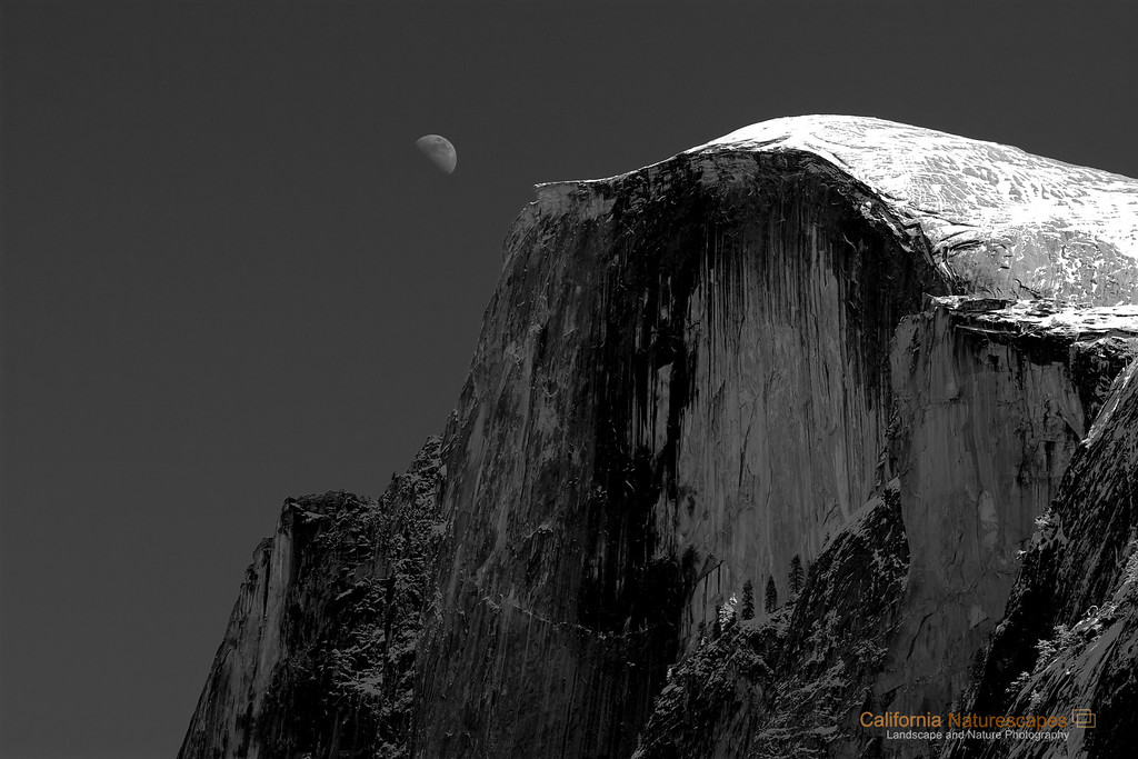 """Half Dome - Half Moon"" Location: Yosemite National Park, California.  The beauty and grandeur of Yosemite was best photographed by late <a href=""http://en.wikipedia.org/wiki/Ansel_Adams"">Ansel Adams</a>. This is tribute to his work. The Half Dome is the iconic rock of Yosemite and is a very popular hiking destination in the valley. Apparently half of it was sheared off by glaciers giving it its name.  Tech Info and Tip: Lens: Canon EF 70-200 f/4L IS at 100mm Camera: Canon EOS 30D Exposure: 1/125sec at f/5.0 and ISO 100 Filters: No filters  Using red filter while converting to b&w can have interesting effects in the sky. A red filter typically darkens the sky which I like for images like this. <br><br>Yosemite is the arguably the most beautiful national park. It's grandeur and the time scale it took to evolve is very humbling. I learnt that the granite peaks started out as molten magma deep below the earth's surface about 100 million years ago. Merced river then carved it into a ""V"" shaped valley and finally glaciers shaped it into its present day ""U"" shape. The beauty of the valley has inspired many. It's lush forests, tall granite peaks, amazing monoliths and beautiful waterfalls are so pristine that a visit to the park often overwhelms the senses. A visit here at least once in lifetime is a must."
