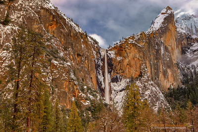 """Bridalveil Falls in Winter"" Location: Yosemite National Park, California.  A bright day after a fresh dusting of snow in Yosemite is a wonderful condition to photograph Yosemite. This spot gets good light during summer when the sun hits directly on the cliff face at sunset. But a combination of clouds and ambient light during winter can be equally appealing. I felt the light on this cliff face was very pleasing on this day and decided to capture this moment.  Tech Info: Lens: Canon EF 24-70mm f/2.8L @ 46mm Camera: Canon EOS 5D Mk II Exposure: 0.3sec at f/16 and ISO 50 Filters: B+W Circular Polarizer  Yosemite is the arguably the most beautiful national park. It's grandeur and the time scale it took to evolve is very humbling. I learnt that the granite peaks started out as molten magma deep below the earth's surface about 100 million years ago. Merced river then carved it into a ""V"" shaped valley and finally glaciers shaped it into its present day ""U"" shape. The beauty of the valley has inspired many. It's lush forests, tall granite peaks, amazing monoliths and beautiful waterfalls are so pristine that a visit to the park often overwhelms the senses. A visit here at least once in lifetime is a must."