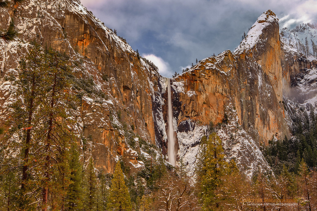 """Bridalveil Falls in Winter"" <br>Location: Yosemite National Park, California.  <p></p><p>A bright day after a fresh dusting of snow in Yosemite is a wonderful condition to photograph Yosemite. This spot gets good light during summer when the sun hits directly on the cliff face at sunset. But a combination of clouds and ambient light during winter can be equally appealing. I felt the light on this cliff face was very pleasing on this day and decided to capture this moment.  </p><p>Tech Info: <br>Lens: Canon EF 24-70mm f/2.8L @ 46mm <br>Camera: Canon EOS 5D Mk II <br>Exposure: 0.3sec at f/16 and ISO 50 <br>Filters: B+W Circular Polarizer  <br><br>Yosemite is the arguably the most beautiful national park. It's grandeur and the time scale it took to evolve is very humbling. I learnt that the granite peaks started out as molten magma deep below the earth's surface about 100 million years ago. Merced river then carved it into a ""V"" shaped valley and finally glaciers shaped it into its present day ""U"" shape. The beauty of the valley has inspired many. It's lush forests, tall granite peaks, amazing monoliths and beautiful waterfalls are so pristine that a visit to the park often overwhelms the senses. A visit here at least once in lifetime is a must.</p>"