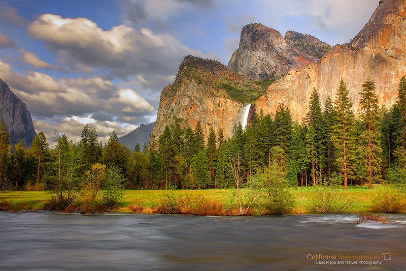 """""""Bridal Veil Falls: A Spring Evening"""" <br>Location: Valley View, Yosemite National Park, California.   <p></p><p>Here is the view of the bridal veil falls lit by the late afternoon sun. It is amazing to me how many different views of this location I have witnessed over the years. Changing lighting conditions, seasons, snow, rain storms, clouds all play a key role in emphasizing the beauty of this location.  </p><p>This view was captured on a spring afternoon prior to arrival of a rain storm. Without clouds not just the sky would have been empty but also there would have been no penetrating light on the granite walls. It's a rare moment that I was very happy to capture!  </p><p>Tech Info: <br>Lens: Canon EF 17-40mm f/4L @ 40mm <br>Camera: Canon EOS 5D Mk II <br>Exposure: 3.2sec at f/16 and ISO 50 <br>Filters: Hoya 8-stop solid ND filter to allow long exposure of 3.2sec. LEE 0.9 (3-stop) soft edge ND grad filter to balance exposure of sky with the foreground.  <br><br>Yosemite is the arguably the most beautiful national park. It's grandeur and the time scale it took to evolve is very humbling. I learnt that the granite peaks started out as molten magma deep below the earth's surface about 100 million years ago. Merced river then carved it into a """"V"""" shaped valley and finally glaciers shaped it into its present day """"U"""" shape. The beauty of the valley has inspired many. It's lush forests, tall granite peaks, amazing monoliths and beautiful waterfalls are so pristine that a visit to the park often overwhelms the senses. A visit here at least once in lifetime is a must.</p>"""