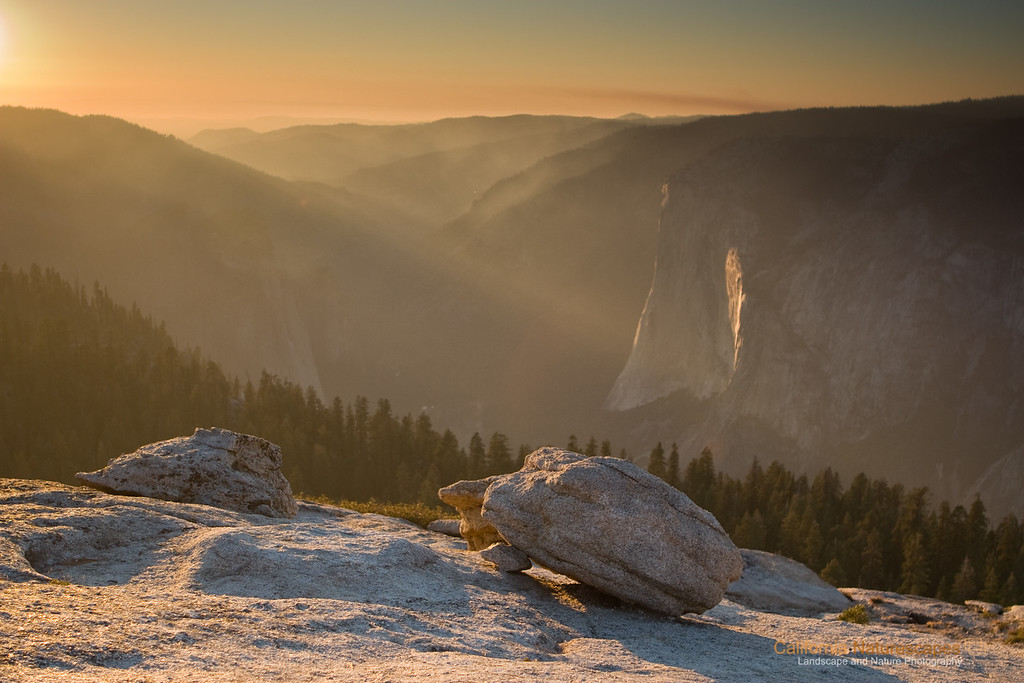 """Sentinel Dome Sunset"" Location: Yosemite National Park, California.  I am posting this image from Yosemite that I captured back in 2007. I have not been to Yosemite for a while now and I am starting to get an itch to pay another visit soon. In the mean time I was going through images from the past and came across this image. Looking at it now I really like it. The warmth of sunlight glow on the glacial erractic boulder brings back the memory of the hike we did on that Nov. evening. So here it is.  Tech Info: Camera: Canon EOS 30D Lens: Canon EF 24-70 f/2.8L @ 28mm Exposure: 1/200sec at f/2.8 and ISO 100 Filters: 2 Stop Singh Ray ND Grad filter <br><br>Yosemite is the arguably the most beautiful national park. It's grandeur and the time scale it took to evolve is very humbling. I learnt that the granite peaks started out as molten magma deep below the earth's surface about 100 million years ago. Merced river then carved it into a ""V"" shaped valley and finally glaciers shaped it into its present day ""U"" shape. The beauty of the valley has inspired many. It's lush forests, tall granite peaks, amazing monoliths and beautiful waterfalls are so pristine that a visit to the park often overwhelms the senses. A visit here at least once in lifetime is a must."