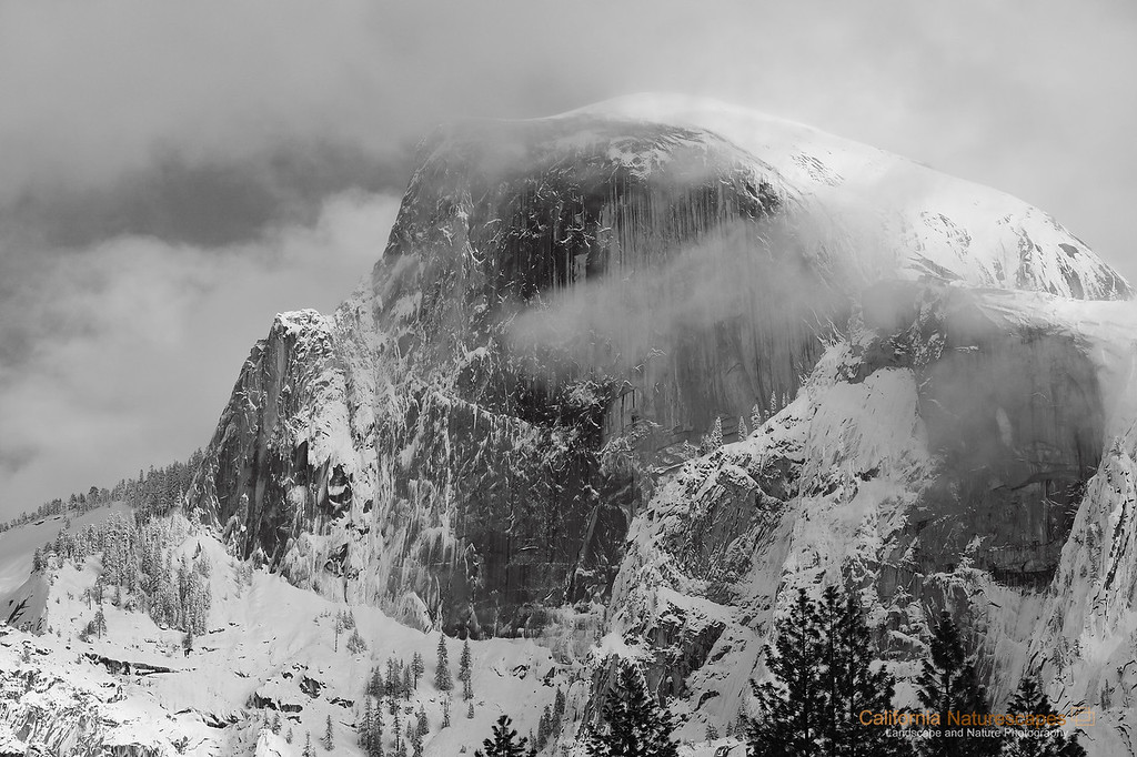 """snow Covered Half Dome"" Location: Yosemite National Park, California.  Certain conditions in Yosemite last for a very short duration. A snow covered and fog shrouded view of iconic Half-Dome is not rare but difficult to catch since the snow melts quite rapidly. I was fortunate to visit Yosemite immeidately after a heavy snowstorm and was happy to catch this view.  Tech Info: Lens: Canon EF 70-200 f/4L IS @ 121mm Camera: Canon EOS 5D Mk II Exposure: 1/125sec at f/9 and ISO 200 Filters: B+W Circular Polarizer <br><br>Yosemite is the arguably the most beautiful national park. It's grandeur and the time scale it took to evolve is very humbling. I learnt that the granite peaks started out as molten magma deep below the earth's surface about 100 million years ago. Merced river then carved it into a ""V"" shaped valley and finally glaciers shaped it into its present day ""U"" shape. The beauty of the valley has inspired many. It's lush forests, tall granite peaks, amazing monoliths and beautiful waterfalls are so pristine that a visit to the park often overwhelms the senses. A visit here at least once in lifetime is a must."