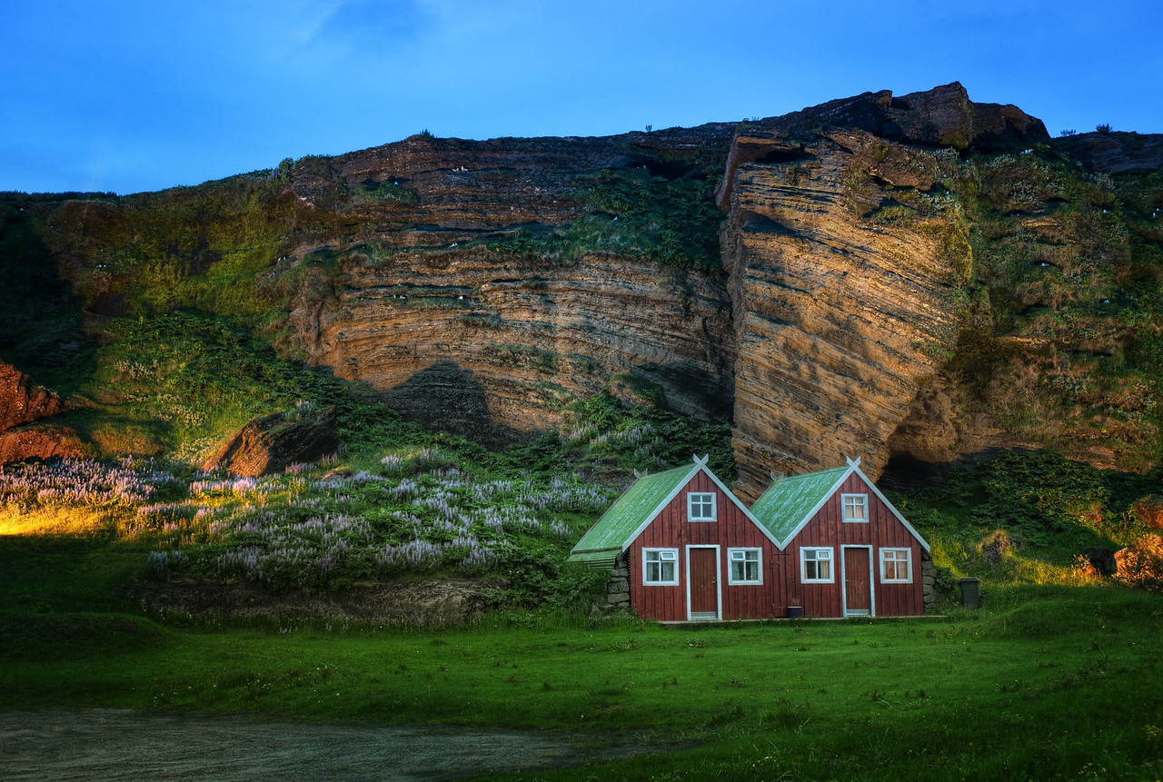 Farmhouse and Roosting Birds at Dusk I only got to stay in this magical place for one night.  If you're really into birds, then you may notice a thing or two about this photo.  Iceland is known for many species of birds, and you can see a bunch of them roosting back in the cliff there.  - Trey Ratcliff  Read more here at the Stuck in Customs blog.