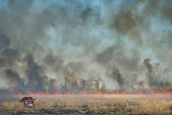 A Garden City Fire Department vehicle drives in a charred field of grass on Burnside Drive Thursday. A fire spread to three fields South of town, and took about an hour for GCFD to get under control.