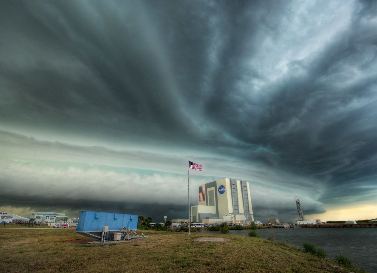 "A Long Day on the Cape I wanted to share this photo I just took of a massive storm sweeping over the complex on the evening before the launch.  I was supposed to be going over to the actual launch pad as night was falling to get a shot, but this storm started to roll in, upsetting those plans. The big structure you see on the other side of the flag is the Vehicle Assembly Building, and that blue structure you see to the left is the famous countdown-clock you always see in front of the press area before the launch.  Right as I was taking this, an official lady from NASA ran into the field warning me that this was now a ""Level 2 lightning alert!""  I happen to be standing by another NASA Tweetup invitee, Lavar Burton.  He asked, ""Is that like a Level 3 diagnostic?""  Greatness.  He was a really cool guy, btw... I put up a photo of us together over on my Facebook Page.  - Trey Ratcliff Read more, including information on the free version of the 100 Cameras in 1 iPad app, here at stuckincustoms.com."