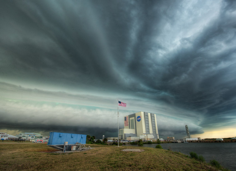"<h2>A Long Day on the Cape</h2> <br/>I wanted to share this photo I just took of a massive storm sweeping over the complex on the evening before the launch.  I was supposed to be going over to the actual launch pad as night was falling to get a shot, but this storm started to roll in, upsetting those plans. The big structure you see on the other side of the flag is the Vehicle Assembly Building, and that blue structure you see to the left is the famous countdown-clock you always see in front of the press area before the launch.  Right as I was taking this, an official lady from NASA ran into the field warning me that this was now a ""Level 2 lightning alert!""  I happen to be standing by another NASA Tweetup invitee, Lavar Burton.  He asked, ""Is that like a Level 3 diagnostic?""  Greatness.  He was a really cool guy, btw... I put up a photo of us together over on <a rel=""nofollow"" href=""http://www.facebook.com/StuckInCustoms"">my Facebook Page</a>. <br/><br/> - Trey Ratcliff <br/><br/>Read more, including information on the free version of the 100 Cameras in 1 iPad app, <a href=""http://www.stuckincustoms.com/2011/04/29/epic-storm-hits-nasa-before-shuttle-launch/"">here</a> at stuckincustoms.com."