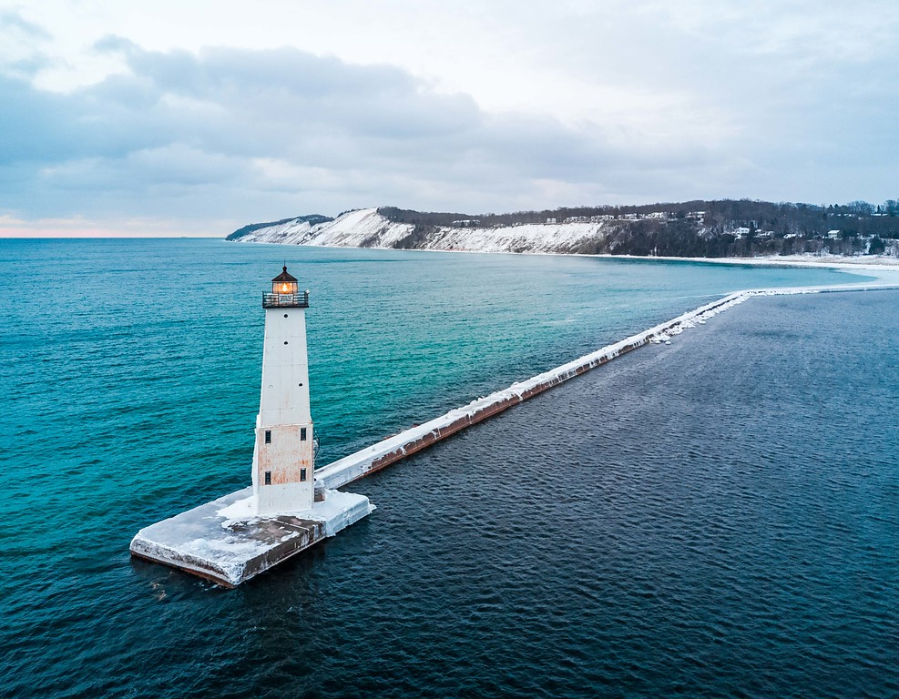 Aerial of the Frankfort North Breakwater Light showing the color change of the Lake Michigan (left, light blue/teal/green) and Frankfort Harbor (right, dark blue) water - March 14th, 2017